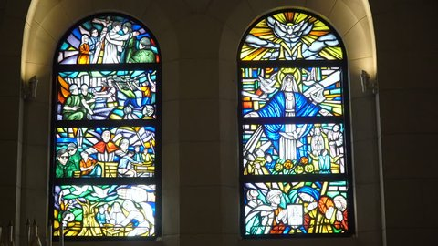 Multicolored stained glass church window illustrated Bible stories. stained glass windows with religious motifs. Manila Cathedral interior, Intramuros. 4K video, Philippines