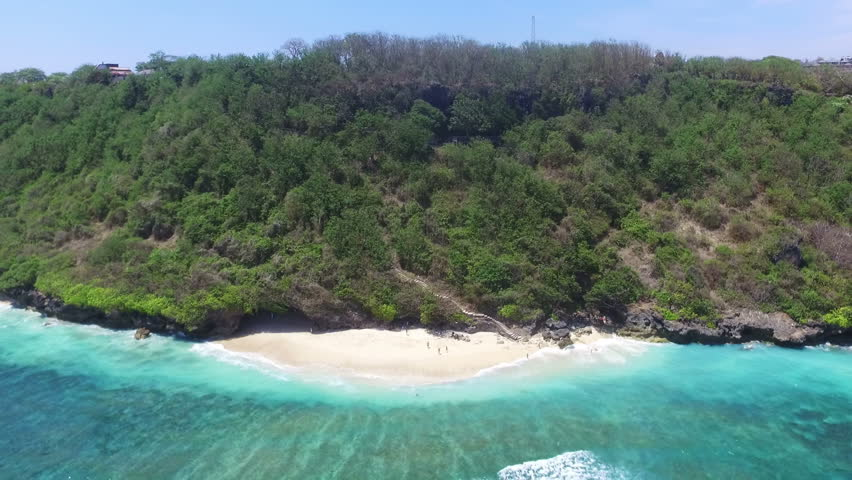 Zoom out aerial view of beautiful tropical forest on island. People walking on sandy beach washed by gentle crystal blue ocean wave