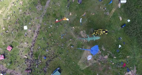 View from great height on kite with shadow and people on green meadow at International Kite Festival
