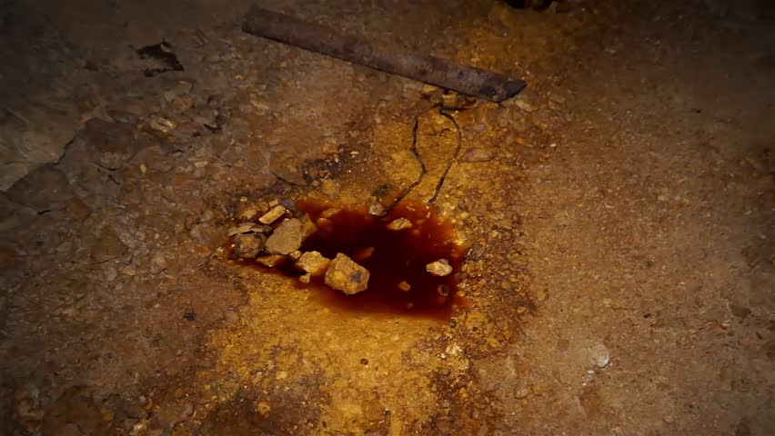 Uranium ore in the depth of a uranium mine. Colored texture. Water of red color from the uranium salts dissolved in it.