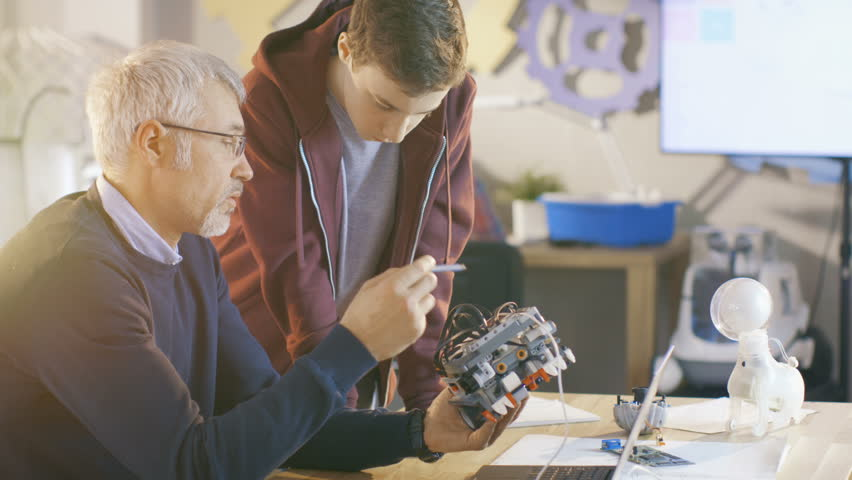 In Computer Science Class Teacher Examines programed Robot Engineered by His Student for School Project. Shot on RED EPIC-W 8K Helium Cinema Camera.