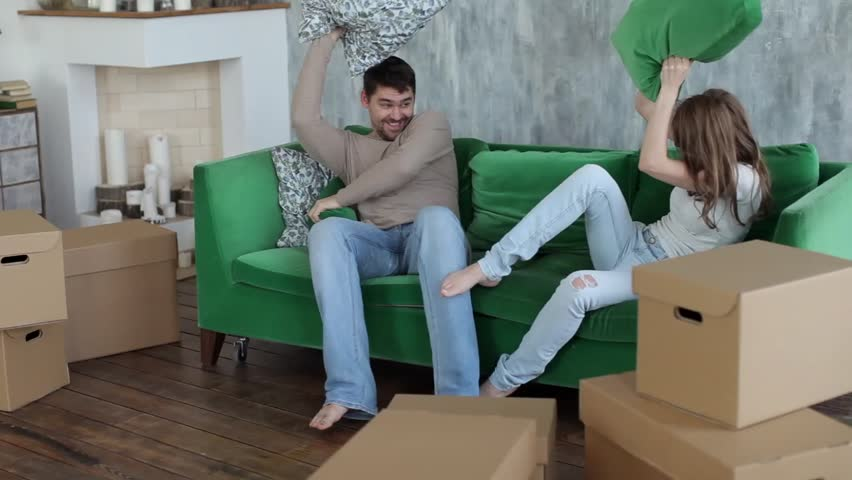Happy Couple Fighting By Cushions Boxes Moving To New Apartment