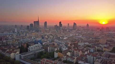 milan city skyline aerial view at sunrise flying backwards