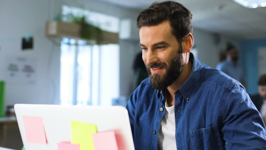 Young attractive bearded man in a blue shirt sitting, using laptop, working in the office, in the background people, smiling | Shutterstock HD Video #27337906