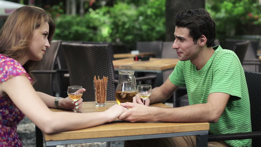 Couple drinking wine and holding hands in cafe