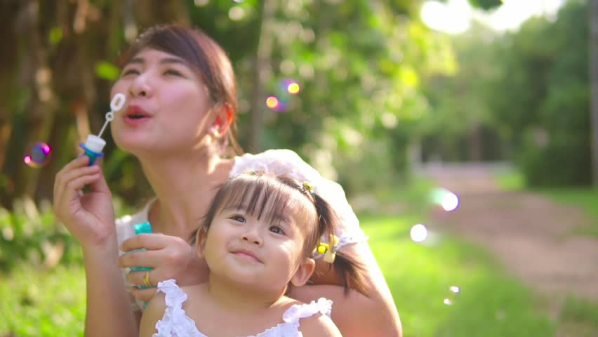 slow motion Asian Mother entertaining her baby girl by making iridescent soap bubbles