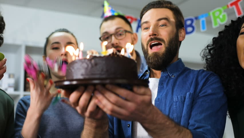 Young business team celebrating a birthday in the office boss blows out the candles | Shutterstock HD Video #27345436