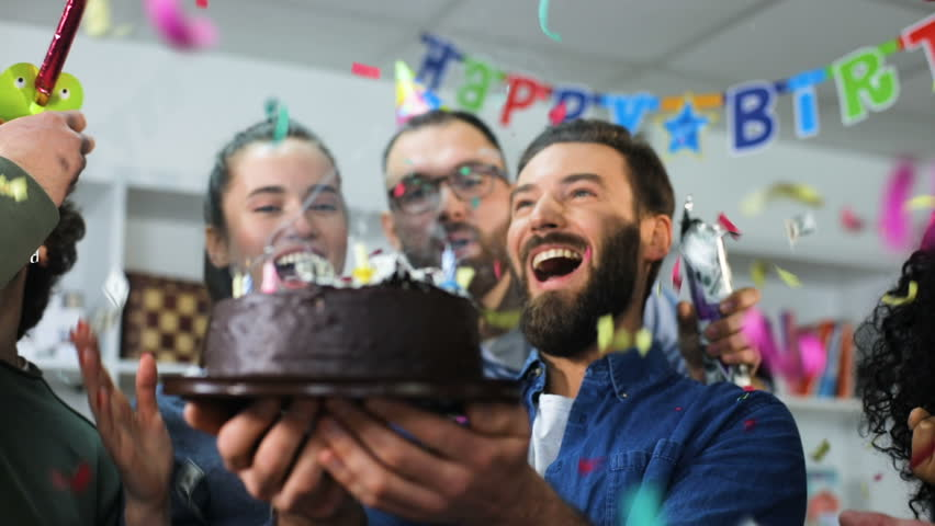 Young business team celebrating a birthday in the office boss blows out the candles