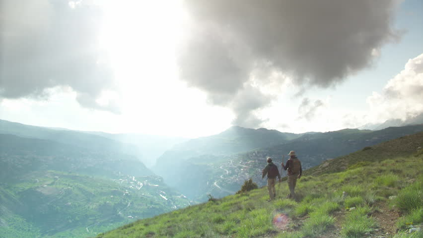 Bsharri, Lebanon. Static shot of two hikers walking down on mountaintop overlooking Bsharri where the last preserved Lebanese Cedar forest is located.