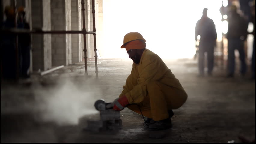 Construction Site, Qatar. View of an asian construction worker wearing a turban and a hardhat using a cutting machine or circular saw.