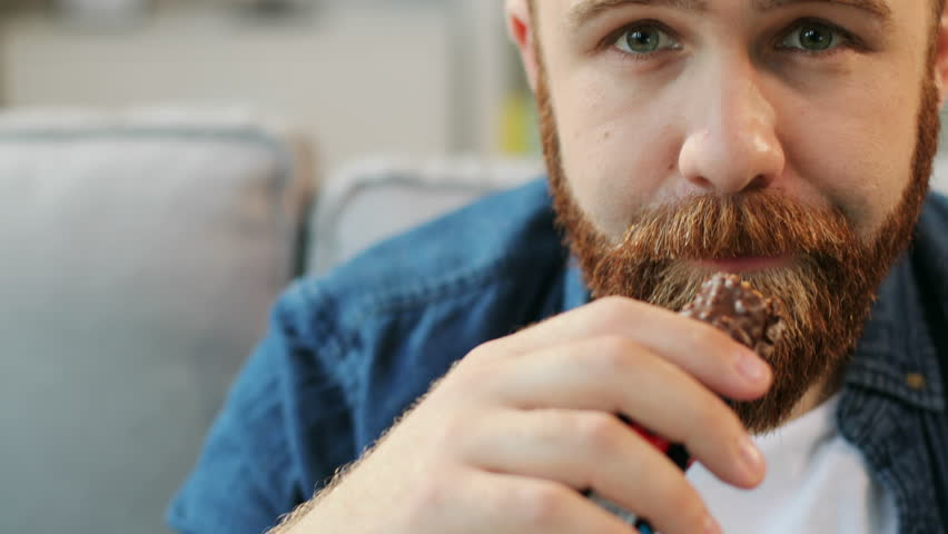 Portrait of hungry hipster man eatting tasty chocolate bar while sitting on sofa at living room background. Close up.