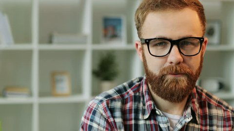 Portrait of serious young man in glasses who start laughting on camera on living room background. Close up.