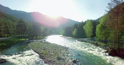 4k (UHD) aerial view. Low flight over fresh cold mountain river at sunny summer morning. Green trees and sun rays.