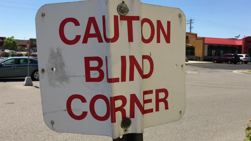Caution blind corner sign that is bent and worn against a bright blue sky. | Shutterstock HD Video #27448426