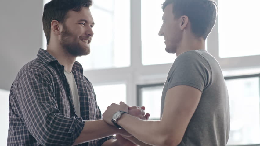 PAN of bearded man in checkered shirt coming towards his male friend and shaking hands in greeting, then chatting before panoramic window on sunny day | Shutterstock HD Video #27462076