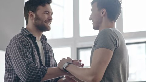PAN of bearded man in checkered shirt coming towards his male friend and shaking hands in greeting, then chatting before panoramic window on sunny day