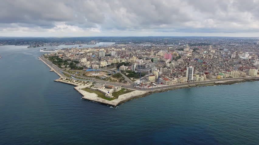 Drone flying over Havana, Cuba: Caribbean sea and Malecon promenade. Aerial view of La Habana skyline, Cuban capital city. Urban landscape seen from the sky with old buildings and ocean