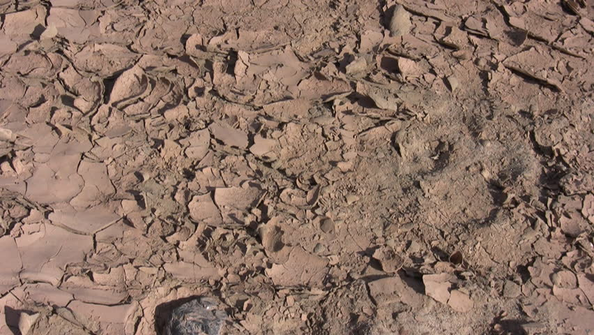 HD pan up of the cracked mud along a dry river bottom to a small water-filled branch of a river