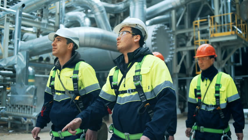 Team of workers walking on fuel plant #27496486