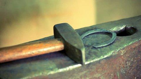 Iron horse horseshoe lie on anvil. Blacksmith making horseshoe for horse on anvil. Close up traditional metal horseshoe on anvil blacksmith