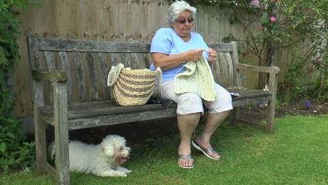 An old woman sitting on a bench, knitting in the shade, with a Bichon Frise dog beneath.
