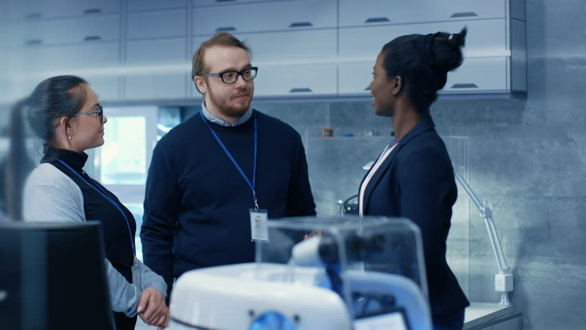 Multi Ethnic Team of Male and Female Leading Scientists Discussing Innovative Robotics Technology They've Building. They Work in a Modern Laboratory/ Research Center. Shot on RED EPIC-W 8K Camera. | Shutterstock HD Video #27516991