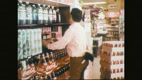 1970s: Man moves bottles on shelf, cleans shelf.
