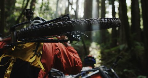 POV Medium angle shot following two mountain bikers as they hike their equipment through a redwood forest in slow motion. Wearing orange jackets. Shot in 4K on RED Epic.