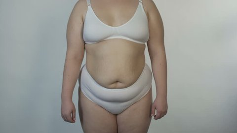 Overweight woman wearing undies posing for camera and turning around, obesity