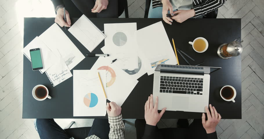 The discussion of four businessmen to solve the business issue using graphics, schedules, laptop. The above view of the hands showing graphics.   Shutterstock HD Video #27562498