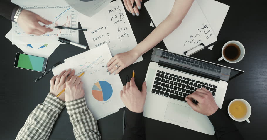 Hands of the businessmen holding the graphics, typing on the laptop. The close-up above view of the business composition.   Shutterstock HD Video #27562531