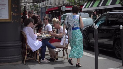 PARIS, FRANCE - MAY 22, 2017: People sit relax eating meals by the tables of cozy street cafe Montmartre Paris