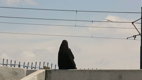 footage of a young woman in chador, a full-body black garment of radical muslim woman
