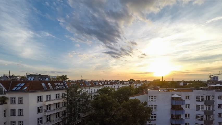 sunset sky over rooftops - time lapse, city skyline
