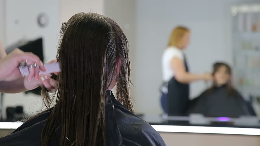 Hairdresser combing and cuting hair of teen girl client in hair salon   Shutterstock HD Video #27577996