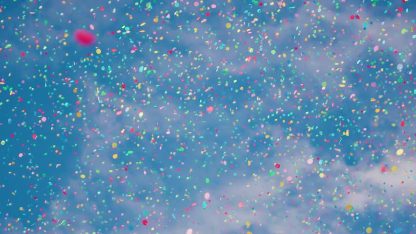 Falling confetti against a summer blue sky. Shot in slow motion