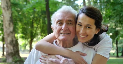 Granddaughter, nurse, caring for the elderly, girl (woman) hugging grandfather, smiling, happy, walking in the park. Concept: boarding house, sanatorium, a house for the elderly, help for the elderly.