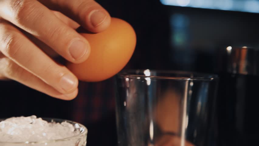 Unrecognisable bartender hand brakes chicken egg and puts it into glass making cocktail close up | Shutterstock HD Video #27592876