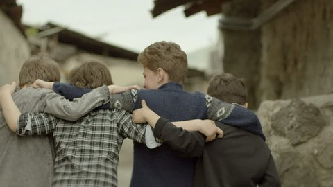 Childhood Memories.  Back view of a group of teen friends walking , hugging each other. Vintage times. Shot on RED EPIC DRAGON Cinema Camera in slow motion.