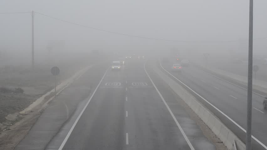 Cars in a highway with dense fog circa January 2012 in Leon, Spain.
