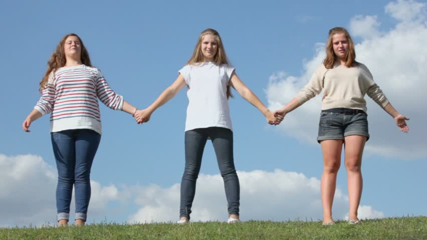 Three young girls hold hands and raise them on grass hill at sunny summer day