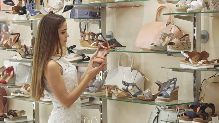 Pretty Young Woman Taking High Heel Sandals From The Rack At Shoe Gorgeous Brown Haired Turning To Camera Boutique