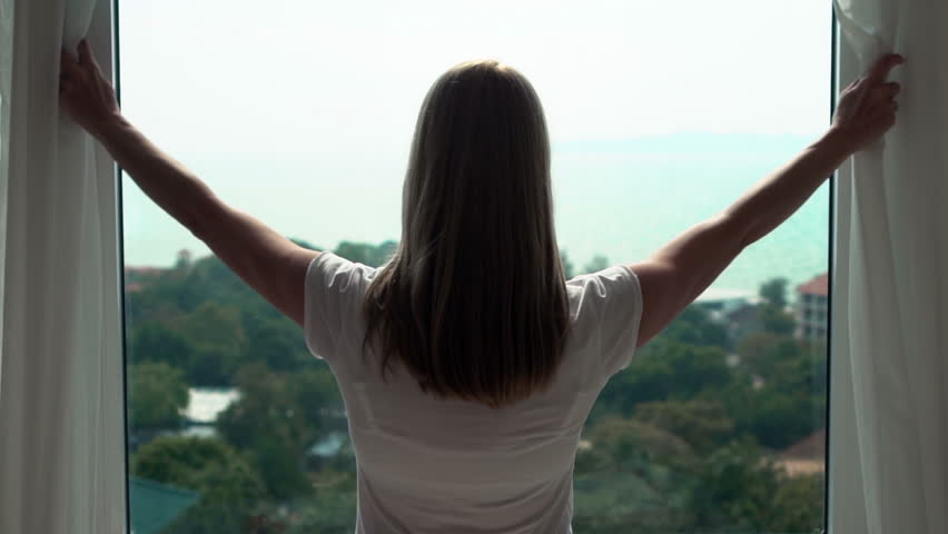 Young woman in white t-shirt opening curtains and looking out of window enjoying the sea view. #27633316