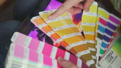 Color model Pantone, PMS (Pantone Matching System). Female hands hold a fan pantone - a choice of colors for the future product. Color Palette Guide. Creative people workplace