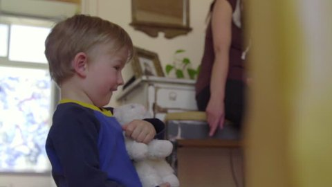 Little boy sees camera and then tries to show it his white toy cat