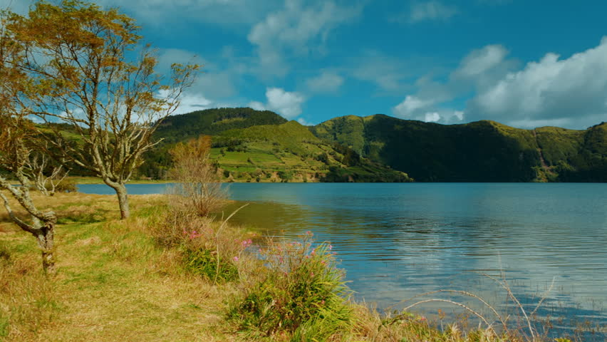 Quaint rural shot of the Blue Lake in Lagoa das Sete Cidades, Sao Miguel Island, The Azores, Portugal on a sunny day. The Azores are one of the hidden gem destinations in Europe.