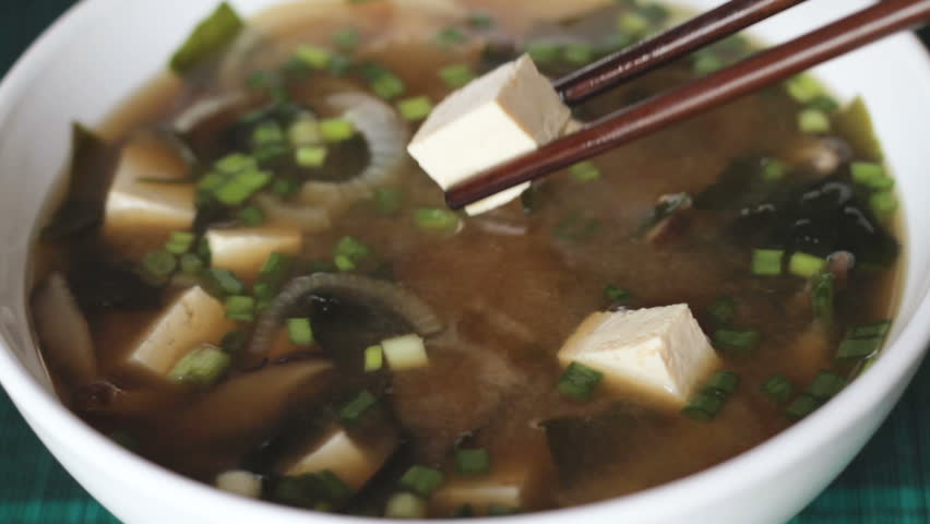 Close up of picking up a dice of tofu with chopsticks from big white bowl of miso soup. It is traditional japanese food. Main ingredients are miso paste, tofu, wakame seaweed and shiitake mushrooms.