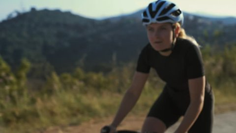 Close up soft focused shot of female athlete cyclist climbing dramatically up the difficult climb breathes deeply as the excersize gets harder, training plan to reach her goals for healthy lifestyle