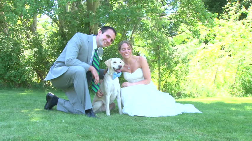 Model released bride and groom with their dog, posing for portraits on their wedding day.