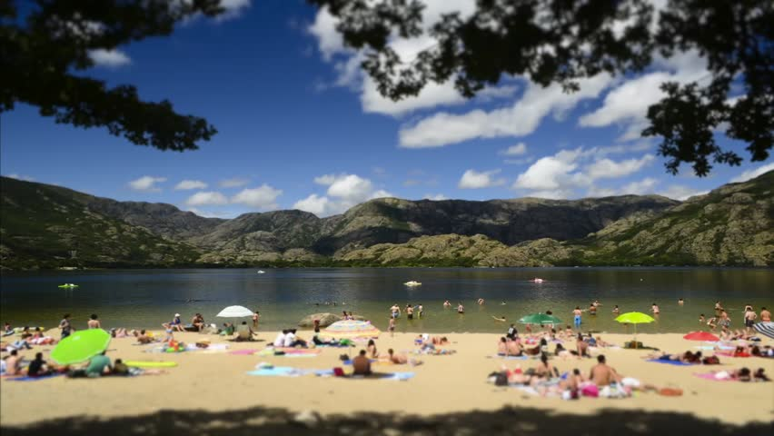 Time lapse of people in the beach of Sanabria Lake Natural Park circa August 2012 in Sanabria, Spain. People blurred and unrecognizable.